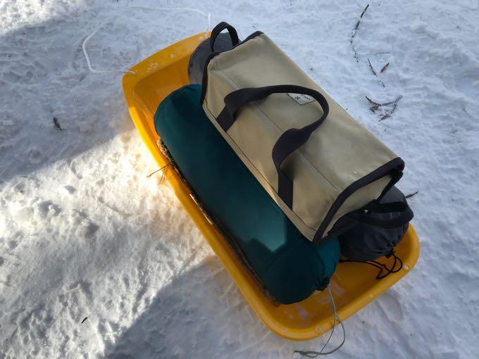 キャンプ道具をソリで運ぶ