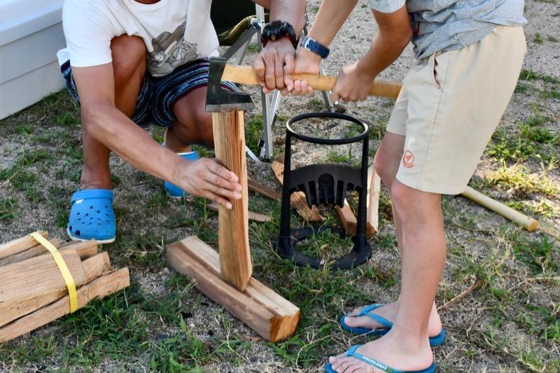 子供が斧で薪割り