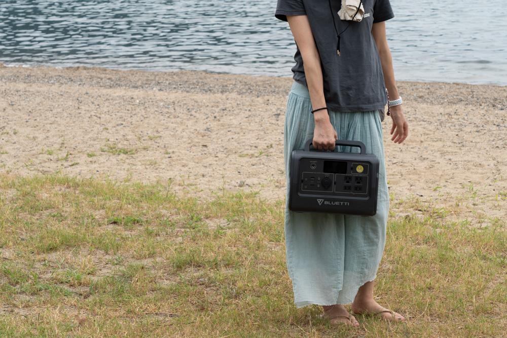 ポータブル電源を女性が運ぶ